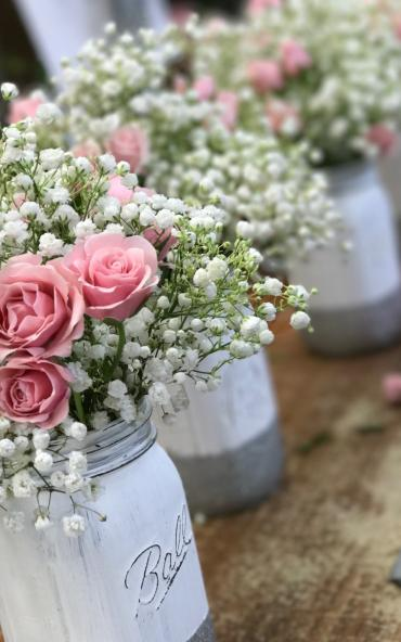 Mason jar centerpieces with spray roses and babies breath