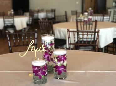 Orchid table arrangement with floating candles
